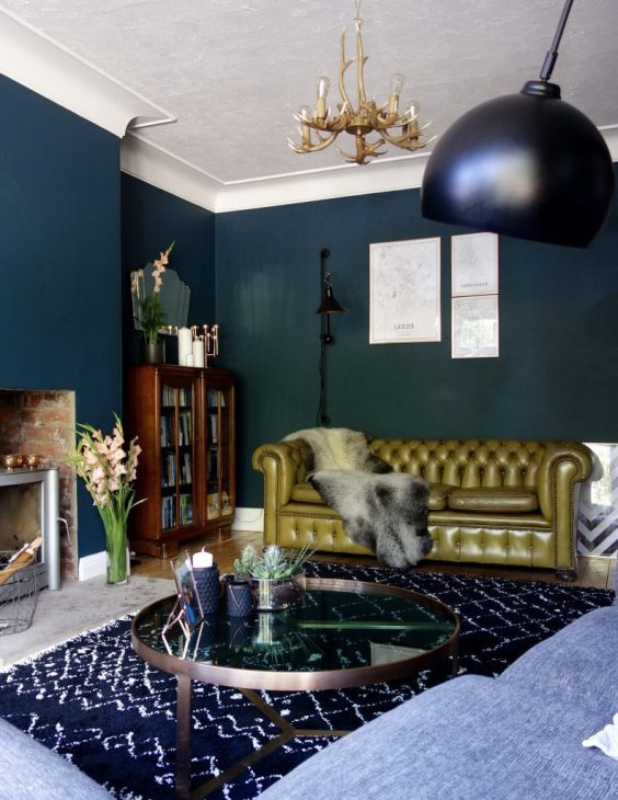 grey-faux-fur-throw-olive-green-chesterfield-sofa-industrial-lighting-dark-green-walls-eclectic-interior-modern-living-room