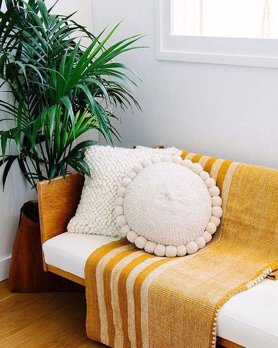 mustard-blanket-wooden-framed-sofa-white-cushions-woven-pillow-indoor-plants-modern-living-room