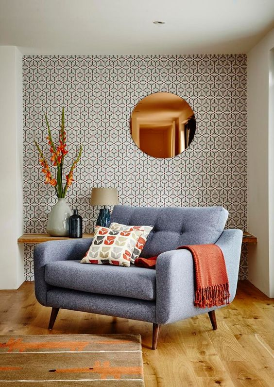 orange-blanket-blue-armchair-tinted-mirror-wallpaper-flowers-modern-living-room